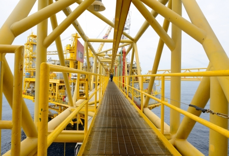greenhouse gas: the worker is walking cross the pathway bridge of offshore oil rig