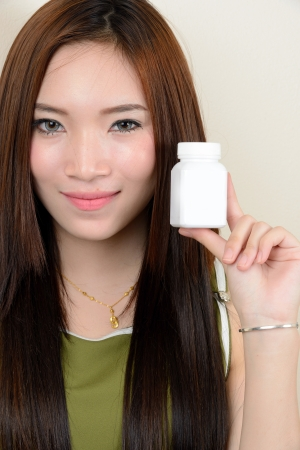 portrait of beautiful  smiling healthy asian woman is holding supplementary food container Standard-Bild