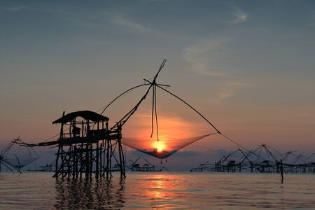 fishery: silhouette traditional fishing method using a bamboo square dip net with sunrise background in Patthalung, Thailand