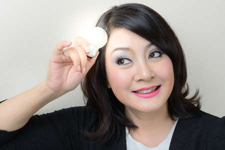 Smiling businesswoman having an idea with bright light bulb over her head photo