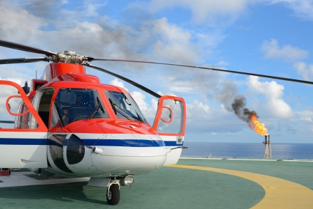 The helicopter park on oil rig to pick up worker with gas flare and blue sky backgroung