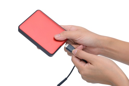 woman hand put USB cable into red external hard disk isolated on white background photo