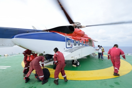 embark: The helicopter landing officer are loading baggage and passenger to embark helicopter at oil rig platform