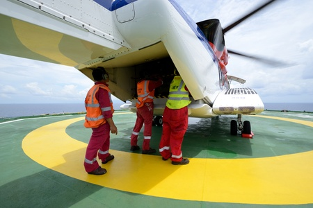 embark: The helideck crew are loading baggage into the cargo ramp of helicopter at oil rig platform Stock Photo