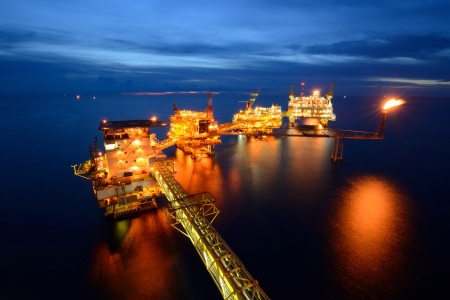 夕暮れの背景との夜に大規模なオフショア石油リグ