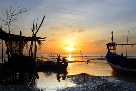 Fisherman are sitting on fishing boat to fix engine with sunrise background at thailand photo