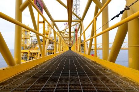trabajador petrolero: el trabajador est? a poca cruzar el puente de la v?a de plataforma petrolera