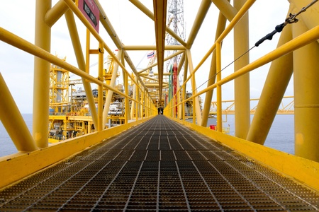 the worker is walking cross the pathway bridge of offshore oil rig