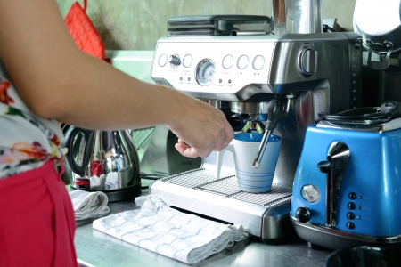 espresso machine: woman make a cup of coffee by coffee machine at home