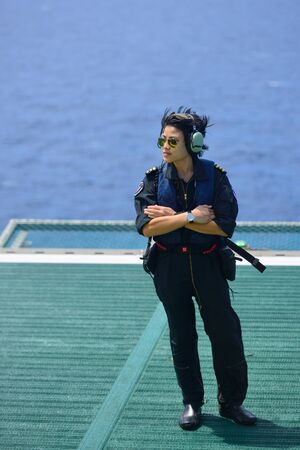 aircrew: asian woman offshore helicopter pilot is standing on offshore oil rig