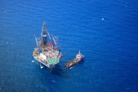 The offshore drilling oil rig and supply boat top view from aircraft