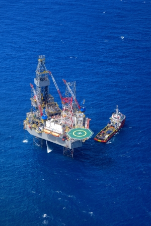 offshore industry: The offshore drilling oil rig and supply boat top view from aircraft