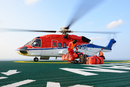 embark: The helicopter landing officer loading baggage to helicopter at oil rig platform Editorial