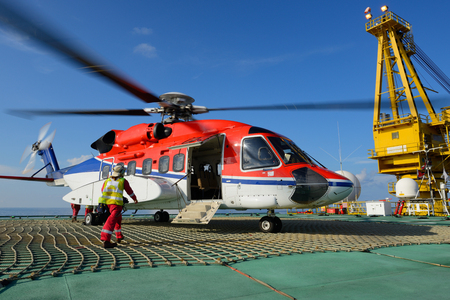 The helicopter landing officer is going to helicopter at oil rig platform Editorial