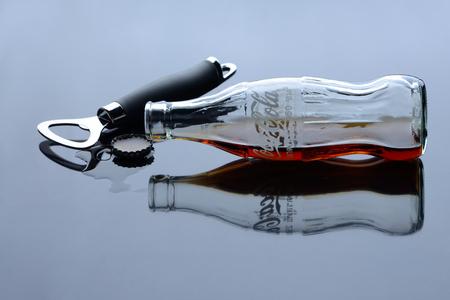 BANGKOK, THAILAND - SEPTEMBER 1, 2012: Classic bottle of Coca-Cola lie next to the bottle opener