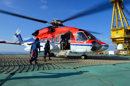embark: The helicopter landing officer take care passenger to embark helicopter at oil rig platform Stock Photo