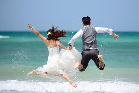 gente saltando: feliz pareja de j�venes casados ??justos celebrando y divertirse en la playa hermosa