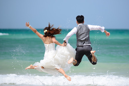 jump suit: happy just married young couple celebrating and have fun at beautiful beach