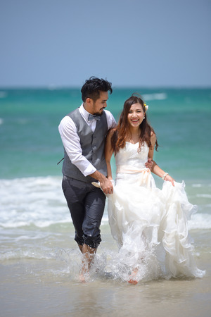 happiness and romantic scene of love just married young couple walking and at beautiful beach