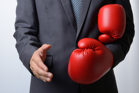 shake off: Businessman remove red boxing gloves to offer a handshake on white background,compromise concept