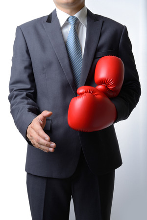 Businessman take off red boxing gloves to offer a handshake on white background,compromise concept Standard-Bild