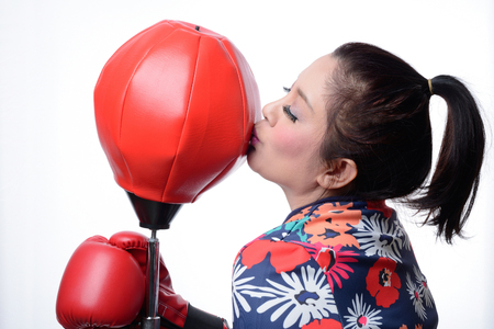 boxing equipment: asian boxing woman kiss red punching bag