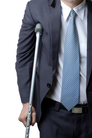 sick leave: injured businessman in with crutches isolated on white background, insurance concept