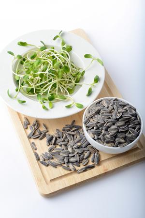 salad plate: verde giovani germogli di girasole su insalata piatto e semi di girasole su sfondo bianco Archivio Fotografico