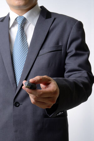 Businessman pushing remote a car key on white background photo