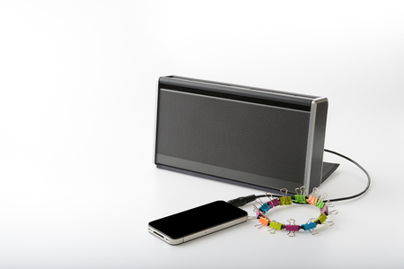 speaker phone: smart mobile phone connect with portable speaker for playing music on white background Stock Photo