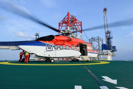 embark: The worker are loading baggage of passenger to helicopter at oil rig platform