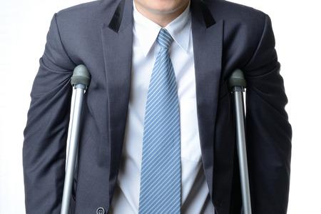 lesionado: hombre de negocios lesionado con muletas aislados sobre fondo blanco, el concepto de seguro Foto de archivo