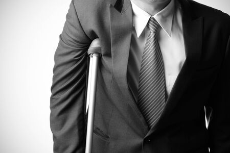 injured businessman in with crutches isolated on white background, insurance concept photo