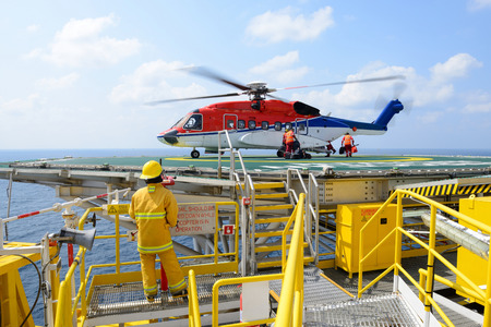 embark: The landing officer are loading baggage of passenger to helicopter at oil rig platform Stock Photo
