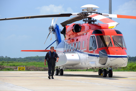 helicopter pilot: offshore helicopter pilot is walking and smiling beside of S92 helicopter at apron