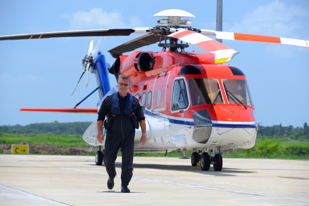 caucasian offshore helicopter pilot is walking and smiling beside of helicopter at apron Standard-Bild