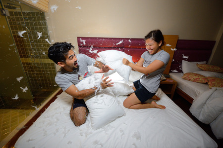 asian wife: happy loving asian couple having a pillow fight in bed at night