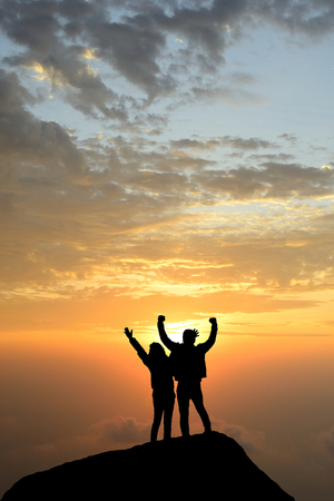silhouette achievements successful both arm up couple is on peak of hill celebrating success with sunrise