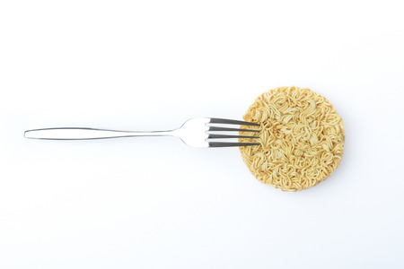 top view of raw instant noodles and stainless fork on white background