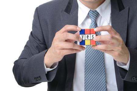 businessman hand playing square puzzle for concept solve solution isolated on white background