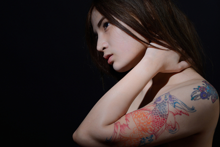 Beautiful asian woman with tattoo on her arm and shoulder,dark background Stock Photo