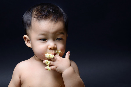 Roztomilé asijské dítě jíst dort s rukou