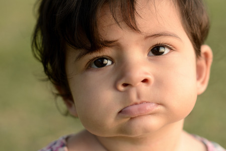 innocense: cute adorable beautiful face of mixed race baby with innocent expression