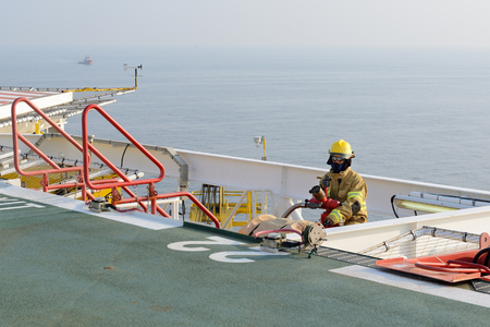 fireman is guarding for offshore helicopter before start up engine at oil rig platform
