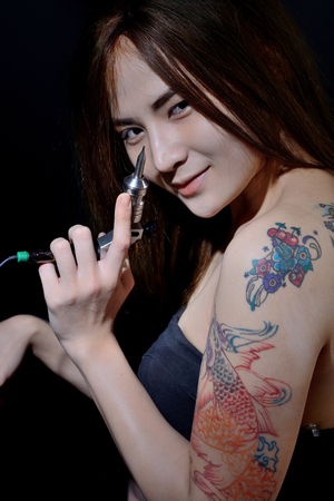 Tattoo asian woman artist holding tattoo machine on dark background Standard-Bild