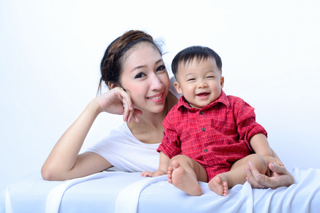 mother baby: Portrait of laughing asian mother and sitting baby on bench