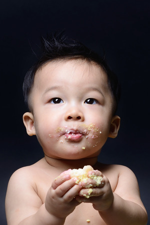 Cute asian baby boy eating cake with his both hand and messy on his face