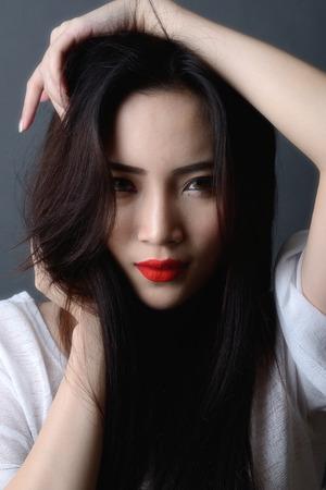 スタジオ撮影、クローズ アップ美しいアジアの女性モデルの黒い髪と赤唇の顔
