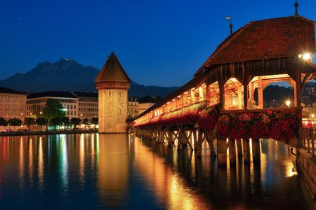 The Water Tower (Wasserturm) beside the Chapel Bridge (Kapellbrucke) in Lucerne Switzerland, during twilight blue hour. Standard-Bild
