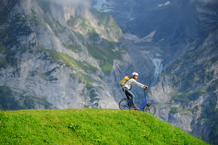 A woman ready to go down from hill by kick scooter at Bort station, Grindelwald Switzerland. Standard-Bild
